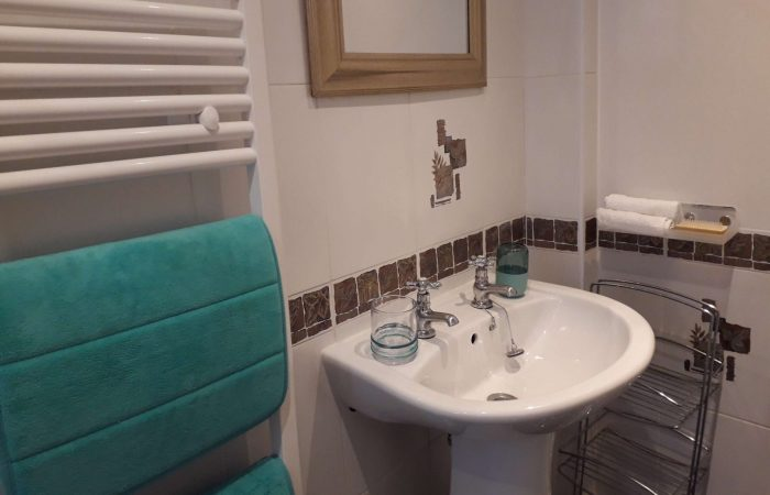Hand basin with mirror above, alongside towel rail8 Church Street Inverness self catering apartment