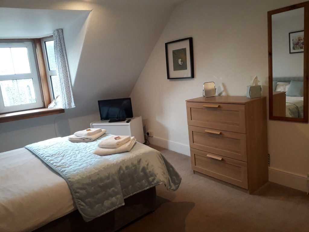 Chest of drawers, mirror, picture in double bedroom