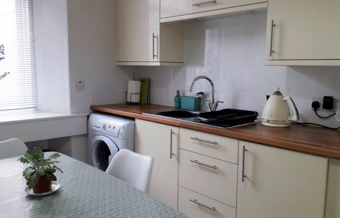Kitchen sink area with washing machine,,units and kettle
