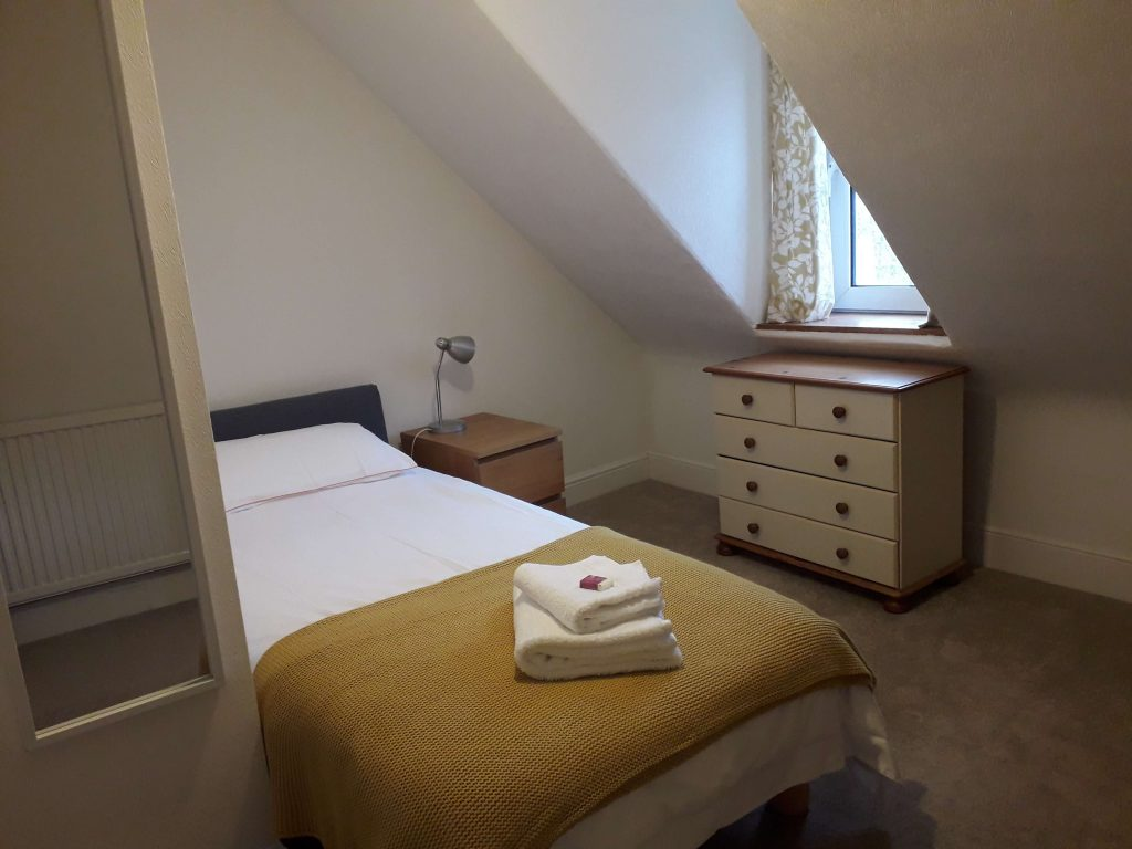 Single bed in carpeted room with chest of drawers.